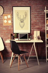 Workplace with laptop, table and bookcase brick wall background