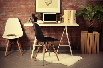 Workplace with laptop, table and chairs on brick wall background