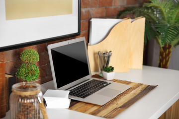 Workplace with laptop, table and stationery on brick wall background