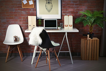Workplace with laptop, table and picture on brick wall background