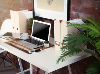 Workplace with table and different devices on brick wall background