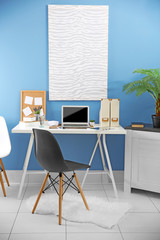 Workplace with different devices, picture, chair and table on blue wall background