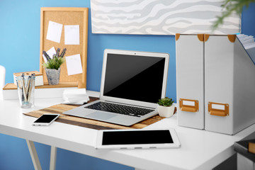 Workplace with different devices, stationery and table on blue wall background