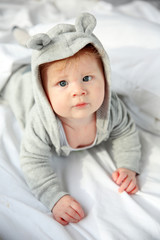 Little baby boy in grey pajamas lying on the bed, close up