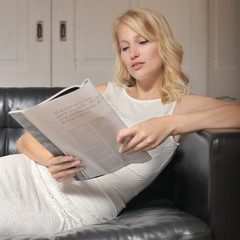 Woman reading while laying on the couch