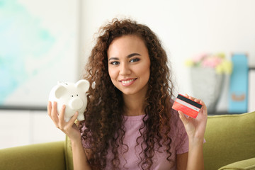 Beautiful young girl with piggy bank  and credit card on armchair