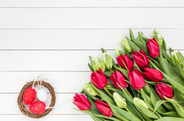 Easter background. Red and white tulips and Easter eggs. Copy space, top view