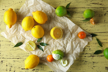 Fresh citrus fruits on a yellow wooden table.
