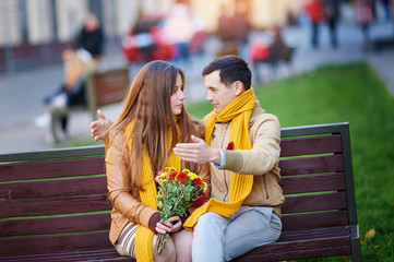 Cute young couple sitting in park bench and talking during date