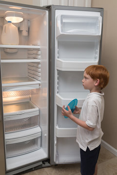 Hungry little boy looks sadly into an empty refrigerator in a poor middle-class home.