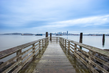 old wood footpath near lake and cityscape of seattle in cloudy s