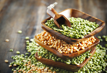 Dry green peas and lentils on wooden background