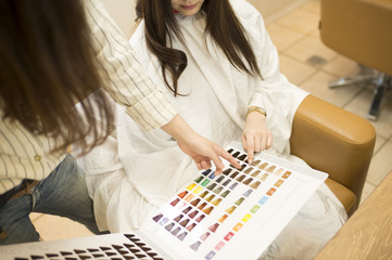Hairdresser is showing the hair of the color swatch to women