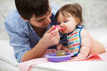 Father feeding baby girl on blanket at home