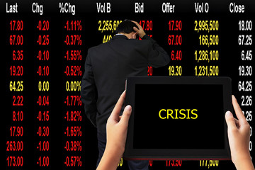 """Financial Concept. """" CRISIS"""" words in yellow on tabled in hands and Young businessman his declining share. Bad business, economy in recession!"""
