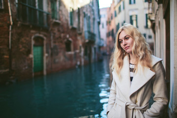 girl in coat standing at the canal in Venice