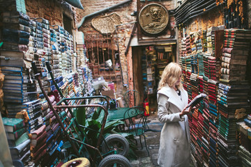 girl reading a book in the backyard of the shop among the pile of books