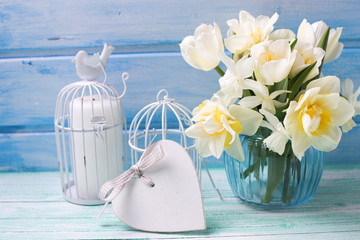 Bright white daffodils and tulips  flowers in blue vase, candles