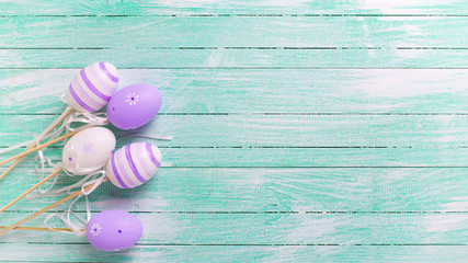 Easter/spring background. Decorative violet eggs on turquoise  w