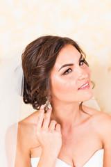 Elegant bride putting on earrings, preparing for wedding