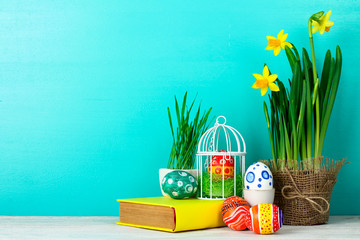 Easter eggs with daffodil in the vase on burlap and book in multicolored covers on a blue wooden background