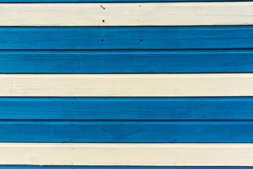 Section of textured blue and white wood panelling from a seaside beach hut. Could be used as a background to illustrate beach and summer holiday themes.