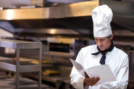 Handsome chef reading menu