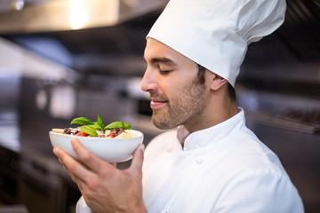 Handsome chef smelling pasta