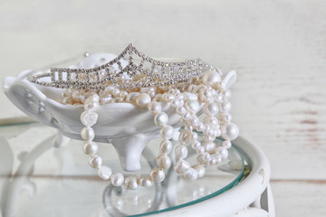 high key image of white pearls necklace and diamond tiara on vintage table