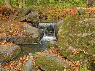 Waterfall surrounded by green mossy stones and fallen leaves in Sofiyivsky Park, Uman City, Ukraine