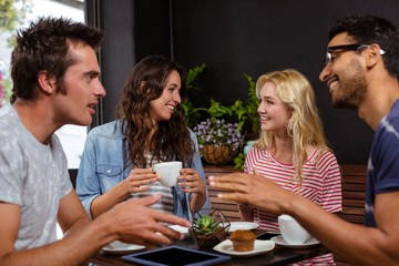 Smiling friends enjoying coffee together