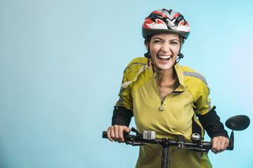 Donna Ciclista con casco su sfondo celeste sorride in camera
