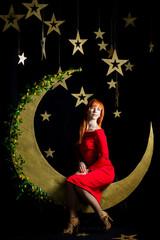 милая рыжая девушка в красном платье не черном фоне