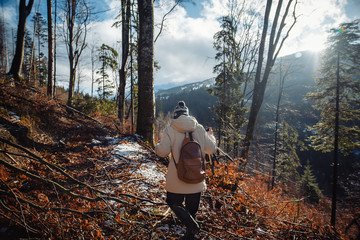 young guy in a warm cap and a jacket with a scarf on the neck, trousers and rubber boots walks alone in the Carpathian mountains with a camera, a tripod and a backpack on his shoulders