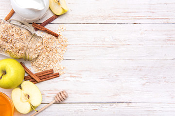 Smoothies with oatmeal, apple and cinnamon in glass jars on a wooden background. Concept of cooking.