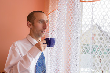 businessman drinking coffee by the window