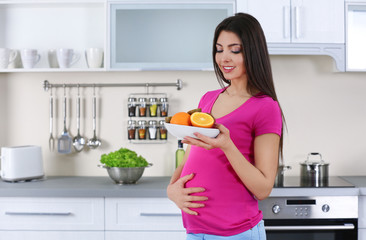Pregnant woman holding plate with fresh juicy fruits in the kitchen