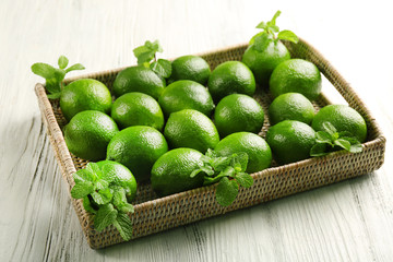 Wicker basket of limes on table