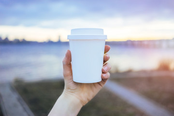 Hand holding paper cup of coffee on natural morning background. Film effect.