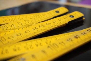 Old yellow folding meter ruler measuring centimeters on the black surface