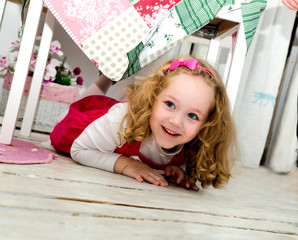 happy little girl on the floor under the table