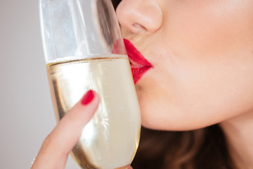 Woman kissing glass of champagne