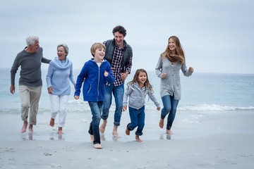 Happy multi-generation family running at sea shore
