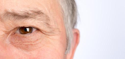 Close-up view on the eye of senior man. Horizontal photo
