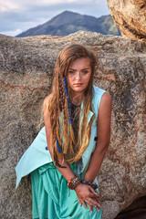 Fashion portrait of young beautiful girl near mountain, boho style