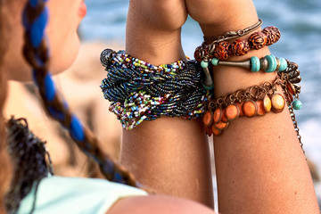 Female hands with bright bracelets, sea wiev
