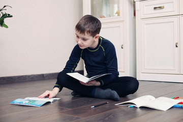 Child does lessons lying on the floor with book