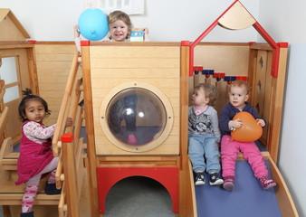 Vier Kinder am Spielgeraet in Krippe oder Kindergarten