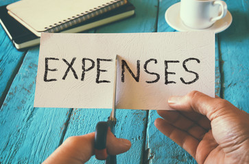 man hand holding card with the word expenses. cutting expenses and costs concept. retro style image