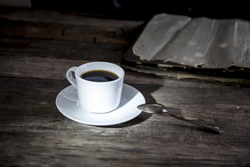 cup of coffee and vintage photos on old wooden table